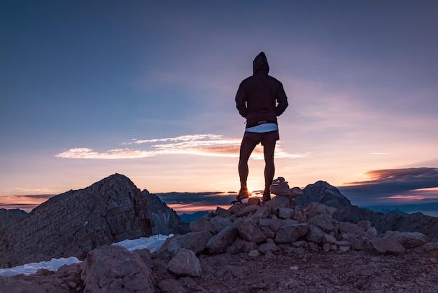 夕日を見ている岩の上に立っている人のシルエット 無料写真
