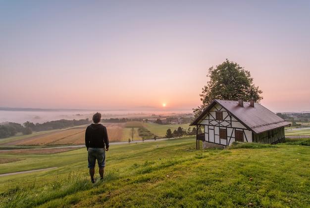 昼間の家と木の近くに立っている人 無料写真