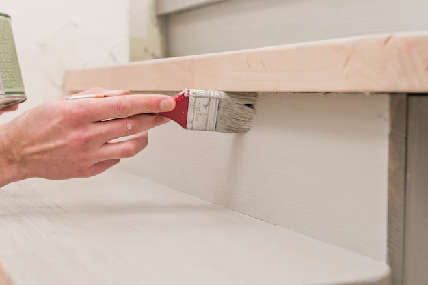 Кисть в руке, нанесение краски на деревянную поверхность во время ремонта Premium Фотографии