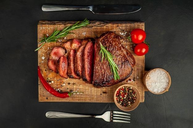 牛肉のグリルステーキ、ハーブ、スパイス、石の背景、トップビューでまな板の上 Premium写真