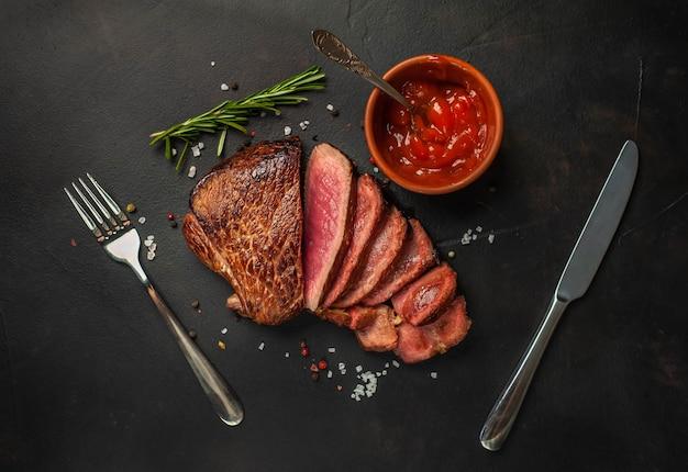 牛肉のグリルステーキ、ハーブ、スパイス、石の背景、上面図 Premium写真
