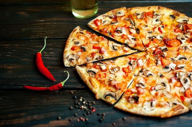 キノコ、トマト、チーズと木のイタリアのピザ Premium写真