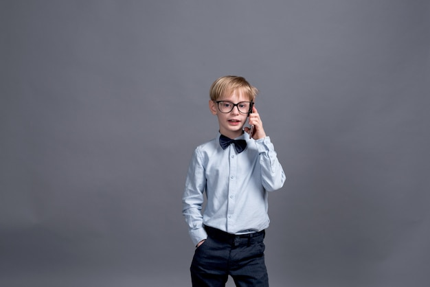Молодой предприниматель, разговаривает по телефону. маленький мальчик позирует на сером Premium Фотографии