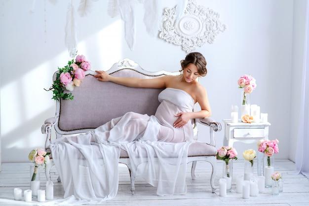 柔らかいインテリアで美しい妊娠中の女性 Premium写真