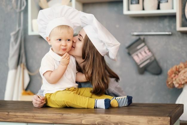 Мать и ребенок на кухне, белые шляпы шеф-повара, мать целует сына, отношения матери и сына Premium Фотографии