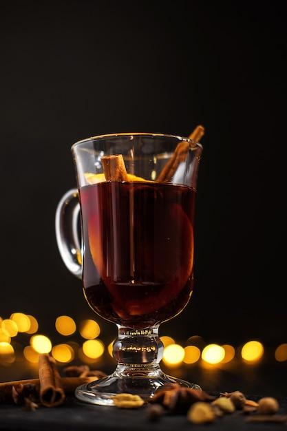 シナモンは、ガラス、オレンジと暗い黒の背景にシナモンとグリューワインのクローズアップガラスにあります。 Premium写真
