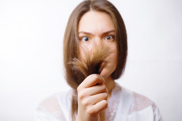 若い女性は彼女の甘やかされて育った髪の端を見て Premium写真