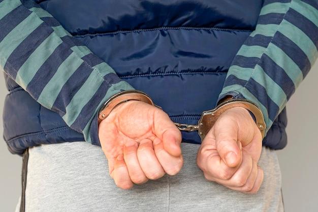 Преступные руки заперты в наручниках. крупным планом Premium Фотографии