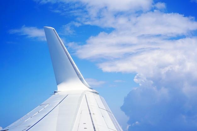 雲の中を飛んでいる飛行機の翼。青い空と白い雲の中の飛行機の翼。 Premium写真