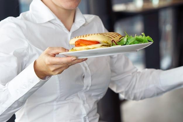 Официант несет тарелку с заказом на каком-то торжественном мероприятии, вечеринке или свадьбе. Premium Фотографии