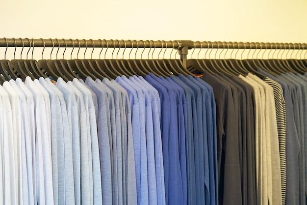 Вешалка для одежды с футболкой. модная одежда на вешалках в магазине. спортивные футболки висят на вешалке для одежды, красочные футболки Premium Фотографии