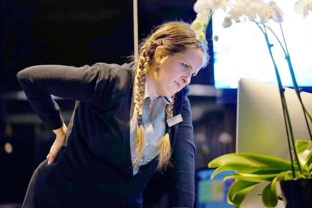 腎臓の痛みを持つ女性受付労働者ホテルマネージャーのクローズアップビュー。腰痛。 Premium写真