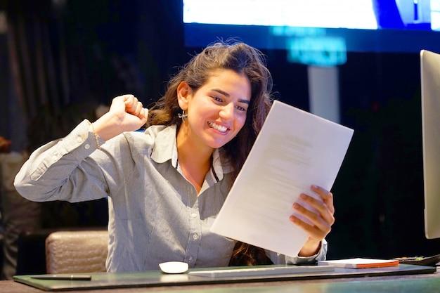 Крупный план офисного работника. счастливая леди, наслаждающаяся хорошими новостями в письменном виде. эйфоричная девушка счастлива после прочтения хороших новостей в письменном письме, одобрения кредита, повышения ее работы. Premium Фотографии