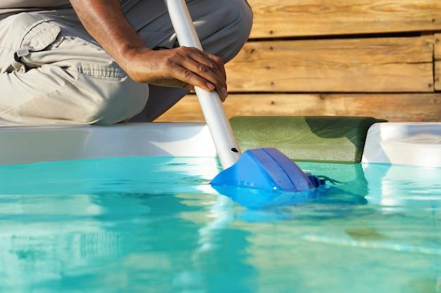 プールを掃除するアフリカのホテルのスタッフ労働者 Premium写真
