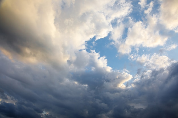 Летний вечер ветер кружит бело-голубые кучевые облака на голубом небе. Premium Фотографии