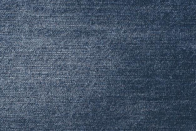 Потертый темный деним. фон синие джинсы. ткань с рисунком. Premium Фотографии