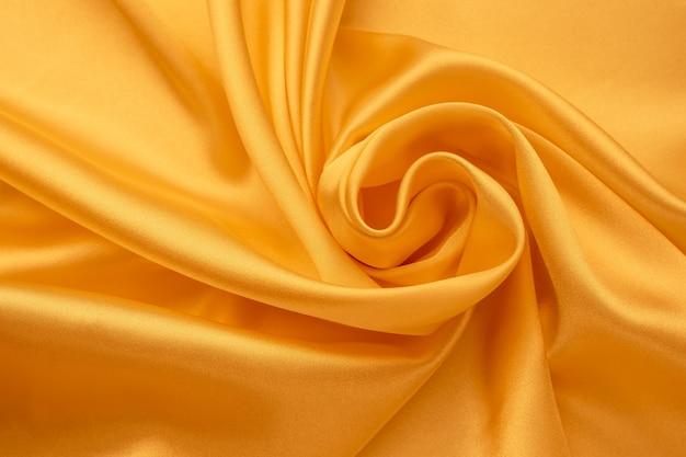 シルクの背景。黄色のサテンの折り目。滑らかな光沢のある生地の質感、抽象的な明るい壁紙。しわくちゃの繊維表面。 Premium写真