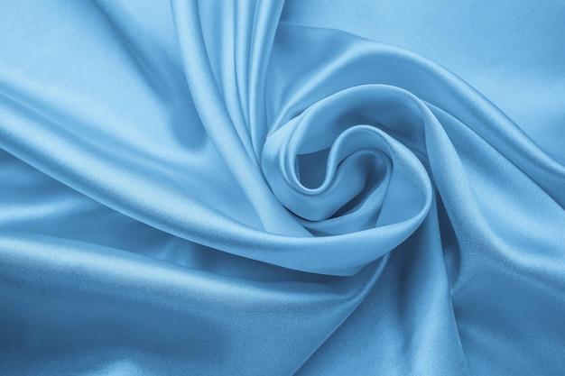柔らかい波状パステル素材、織物の青い光沢のある質感。サテンの折り目、波のパターン。曲線のあるシルキーな背景、高級ファッション。折り畳まれた布、壁紙。 Premium写真