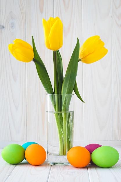 黄色のチューリップと明るい木製の背景にカラフルなイースターエッグの花束。春の花とパスカルのグリーティングカード。 Premium写真