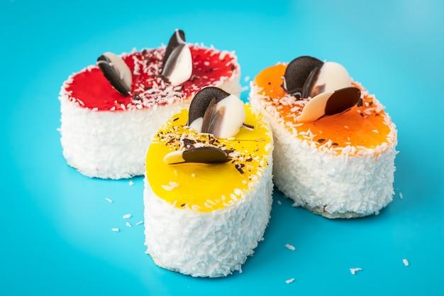 振りかけるケーキ、不健康な高カロリー食品。青の背景にペストリーにココナッツフレーク。自家製焼き色のデザート。 Premium写真