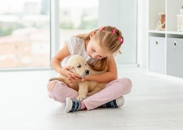 Милая девушка смотря щенка Premium Фотографии