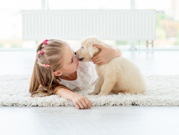 Щенок целует маленькую девочку Premium Фотографии