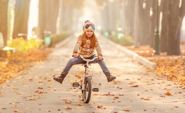 公園で自転車に乗って幸せな女の子 Premium写真
