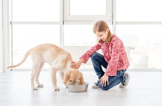 Милая девушка кормит собаку Premium Фотографии