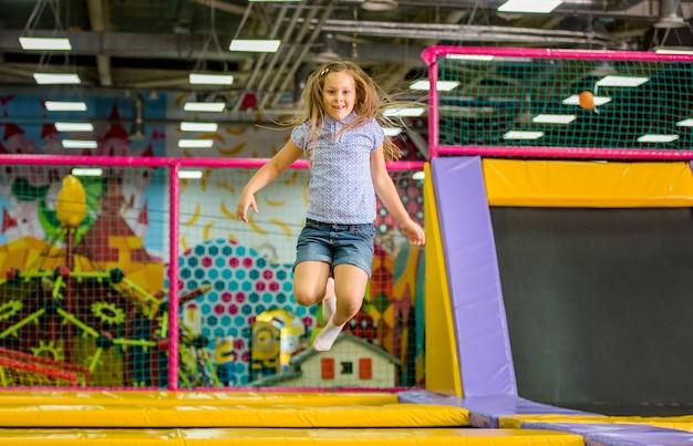Маленькая девочка прыгает на батуте в парке развлечений Premium Фотографии