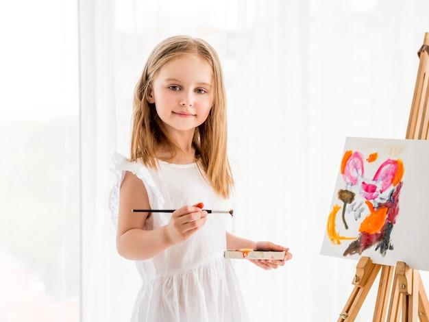 イーゼルに絵を描く少女の肖像画 Premium写真