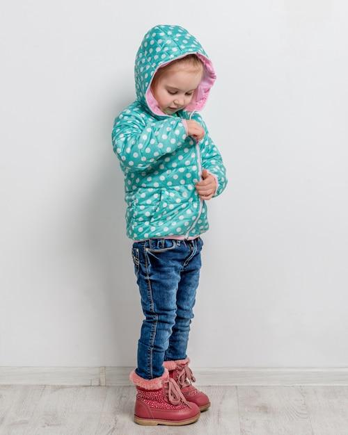 彼女の青いジャケットを締める少女 Premium写真