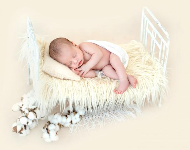 Милый новорожденный лежа на детской кровати Premium Фотографии