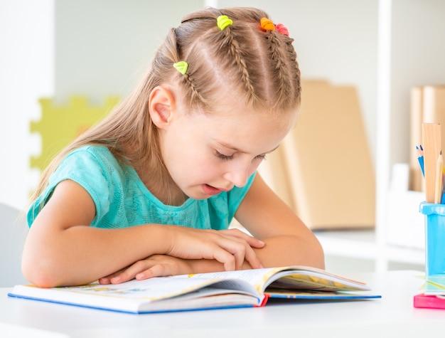 Симпатичная школьница читает книгу, крупным планом Premium Фотографии