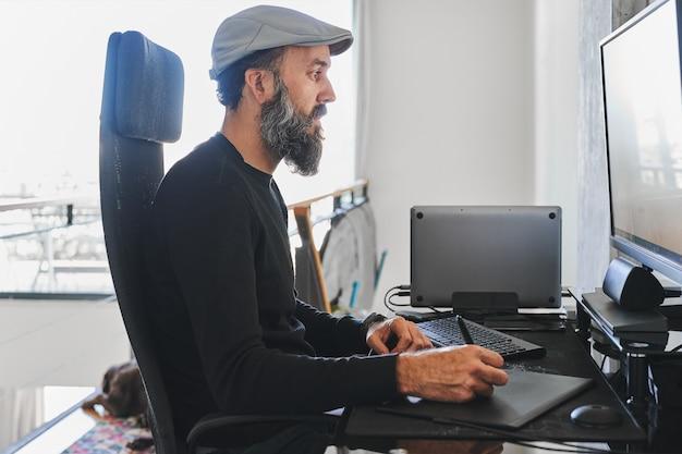 Вид сбоку человека, работающего дома с ноутбуком, внешним монитором и с помощью графического планшета Premium Фотографии