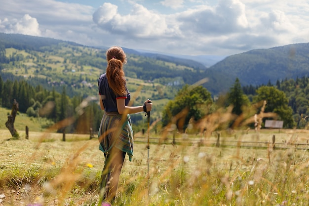 若い女性ハイカーに立って山と谷の遠くの範囲を見渡すマウンテンビューを眺め Premium写真