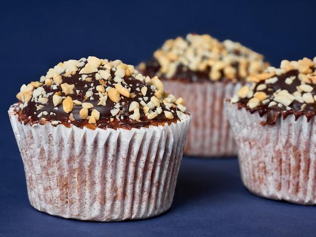 Три кексы с арахисом и шоколадной глазурью в линии на синем фоне. Premium Фотографии