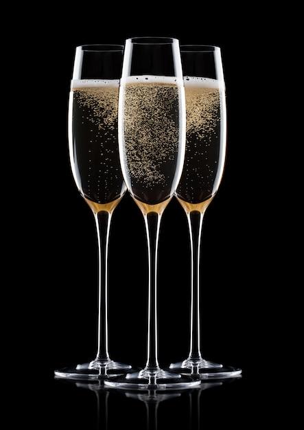 Элегантные бокалы из желтого шампанского с пузырьками на черном фоне с отражением Premium Фотографии