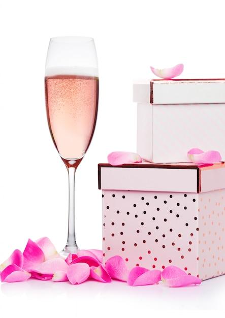 心とピンクのギフトボックスと白い背景のバレンタインデーのバラとピンクのシャンパンのグラス Premium写真