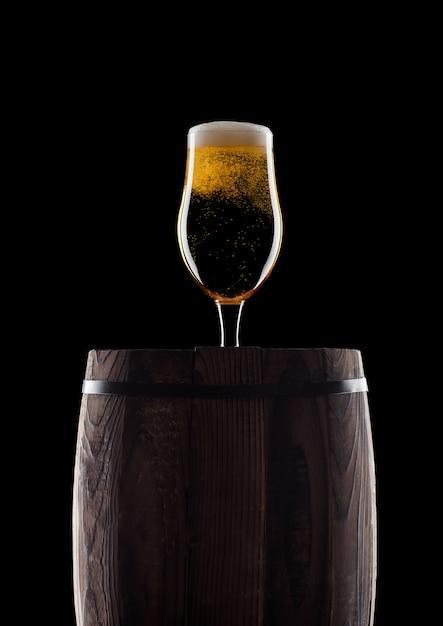 Холодное стекло крафтового пива на старой деревянной бочке на черном фоне с росой и пузырьками Premium Фотографии