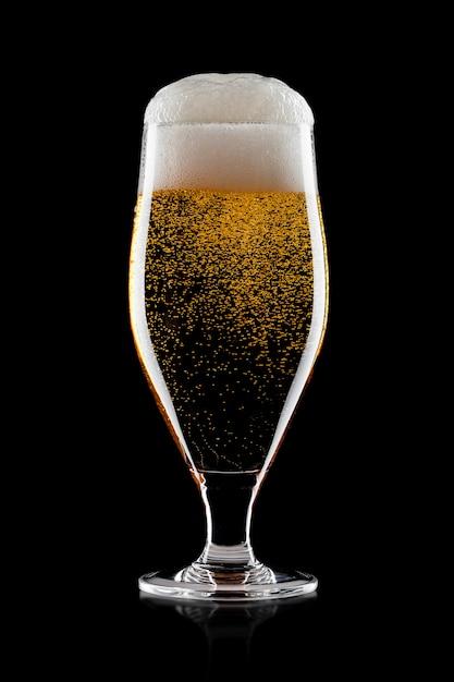 Холодный стакан пива лагер эль крафт с пеной и пузырьками на черном фоне Premium Фотографии