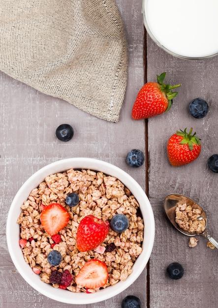 イチゴとブルーベリーと木の板にミルクのガラスと健康的なシリアルグラノーラのボウル Premium写真