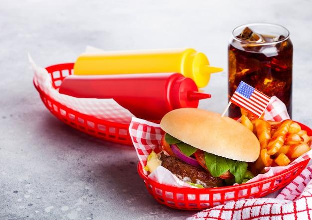 Свежий говяжий бургер с соусом и овощами и стакан колы безалкогольный напиток с картофелем фри фри в красной сервировочной корзине на каменной кухне. Premium Фотографии