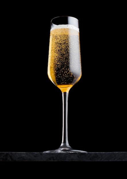 Шикарное стекло желтого шампанского с пузырьками на черной мраморной доске на черном. Premium Фотографии