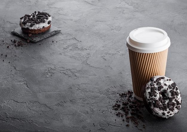黒い石のキッチンテーブルに黒いクッキードーナツと段ボールのコーヒーカップ。カフェドリンクとスナック。 Premium写真