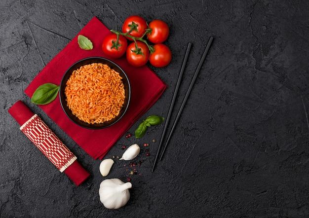 赤いナプキンと竹のランチョンマットにトマトとバジルとニンニクと箸とご飯の黒いプレートボウル。上面図。 Premium写真