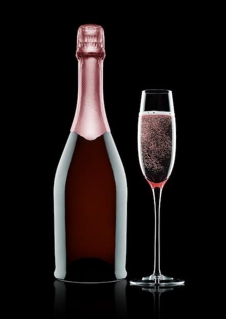 ボトルと黒の背景にピンクのバラシャンパンのグラス Premium写真
