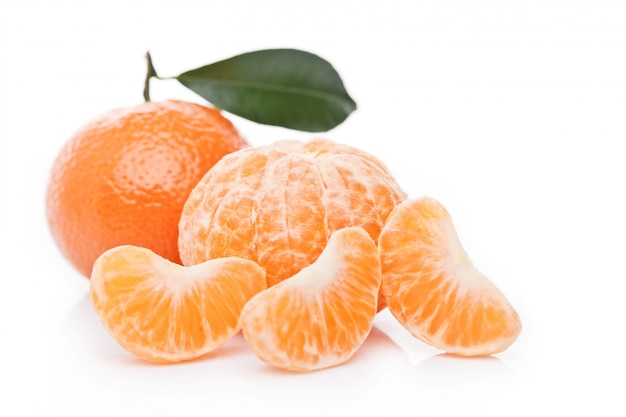 Свежие органические мандарины фрукты мандарины с листьями с очищенными половинками на белом фоне Premium Фотографии