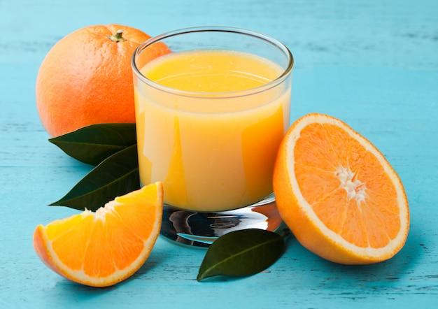 青い木製の背景に生オレンジと有機の新鮮なオレンジのスムージージュースのガラス。 Premium写真