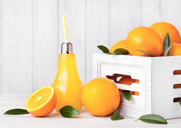 Стеклянная лампа в форме органического свежего апельсинового сока с сырыми апельсинами в белой деревянной коробке Premium Фотографии