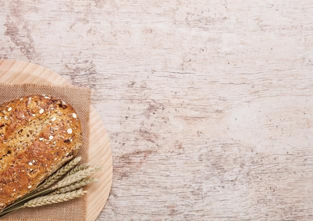 オート麦と木の板の背景にキッチンタオルで焼きたてのパン Premium写真